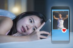 Young sweet and beautiful Asian Chinese woman happy lying on bed using internet mobile phone dating app sending like to attractive stock images