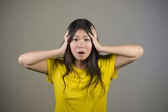 Young sweet and beautiful Asian Korean woman gesturing shocked and surprised as if oh my god what a disaster in astonished face ex. Pression on isolated Royalty Free Stock Images