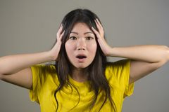 Young sweet and beautiful Asian Korean woman gesturing shocked and surprised as if oh my god what a disaster in astonished face ex royalty free stock photo