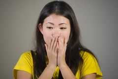 Young sweet and beautiful Asian Korean woman gesturing shocked and surprised as if oh my god what a disaster in astonished face ex. Pression on isolated Royalty Free Stock Image
