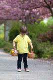 Young sweet boy, carrying two baskets with flower and eggs, walk Stock Photo