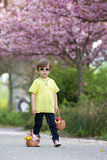 Young sweet boy, carrying two baskets with flower and eggs, walk Stock Images