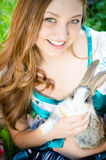 Young sweet brunette smiling girl with a rabbit Stock Image