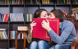 Young Sweet Couple Kissing Behind a Red Book Royalty Free Stock Image