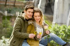 Young sweet couple in love kissing tenderly on street celebrating Valentines day or anniversary cheering in Champagne Stock Images