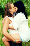 Young sweet couple's passionate cuddle and kiss. Young man and woman kiss and hug one another in white clothes outdoor Royalty Free Stock Images