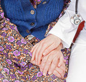 Young sweet doctor holds the old woman's hand. Young doctor holds the old woman's hand Royalty Free Stock Photo