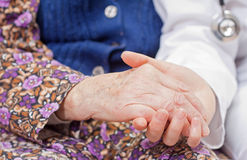 Young sweet doctor holds the old woman's hand. Young doctor holds the old woman's hand Royalty Free Stock Photography