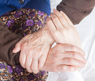 Young sweet doctor holds the old woman's hand Stock Images