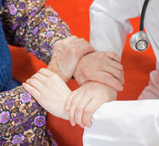 Young sweet doctor holds the old woman's hand Royalty Free Stock Photos