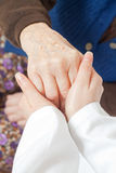 Young sweet doctor holds the old woman's hand. Young doctor holds the old woman's hand Royalty Free Stock Photos