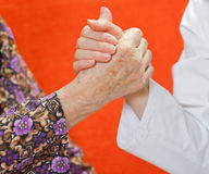 Young sweet doctor holds the old woman's hand Royalty Free Stock Images