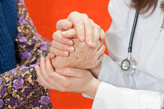 Young sweet doctor holds the old woman's hand Stock Photography