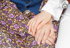 Young sweet doctor holds the old woman's hand. Young doctor holds the old woman's hand Royalty Free Stock Images