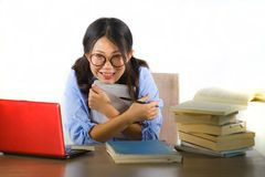 Young sweet and happy Asian Chinese student girl in nerd glasses working cheerful on laptop computer on desk with pile of books royalty free stock image