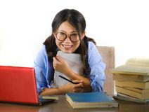 Young sweet and happy Asian Chinese student girl in nerd glasses working cheerful on laptop computer on desk with pile of books royalty free stock photos