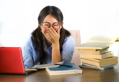 Young sweet and happy Asian Korean student girl in nerd glasses working cheerful on laptop computer on desk with pile of books stock image