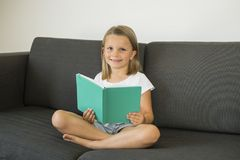 Young sweet and happy little girl 6 or 7 years old sitting on home living room sofa couch reading a book quiet and adorable in chi Stock Images
