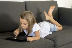 Young sweet and happy little girl 6 or 7 years old lying on home living room sofa couch using internet digital tablet touch pad Stock Photos