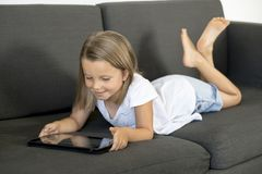 Young sweet and happy little girl 6 or 7 years old lying on home living room sofa couch using internet digital tablet touch pad Stock Photography