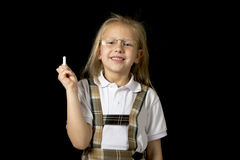 Young sweet junior schoolgirl with blonde hair standing happy and smiling holding chalk royalty free stock photo