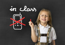 Young sweet junior schoolgirl writing with chalk about not using mobile phone in school class. Young sweet junior schoolgirl with blonde hair standing happy and Stock Photos