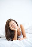 Young sweet lady lying on bed and dreaming Royalty Free Stock Photo