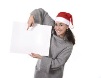 Young sweet Latin woman in Santa Christmas hat pointing blank billboard Stock Image