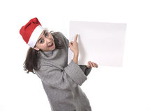 Young sweet Latin woman in Santa Christmas hat pointing blank billboard Stock Photo
