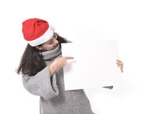 Young sweet Latin woman in Santa Christmas hat pointing blank billboard Stock Photography