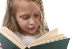 Young sweet little 6 or 7 years old with blond hair girl reading a book looking curious and fascinated Stock Images