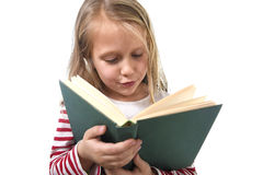 Young sweet little 6 or 7 years old with blond hair girl reading a book looking curious and fascinated Royalty Free Stock Image