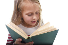 Young sweet little 6 or 7 years old with blond hair girl reading a book looking curious and fascinated Stock Image
