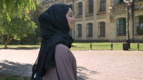 Young sweet muslim girl in hijab is smiling and going to university in daytime in summer, religious concept, studying. Concept, side view stock footage