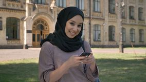 Young sweet muslim girl in hijab is typing message on smartphone in daytime in summer, giggling, building on background. Religiuos concept, communication stock footage