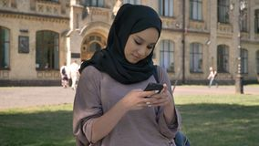Young sweet muslim girl in hijab is typing message on smartphone and smiling in daytime in summer, building on. Background, religiuos concept, communication stock video