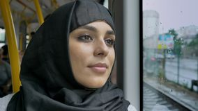 Young sweet muslim woman in hijab is watching in rainy window in bus, transport concept, urban concept, weather concept. Dreaming concept stock video