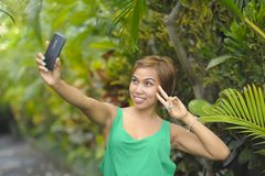 Young sweet and pretty Asian woman holding mobile phone taking selfie picture in tropical jungle smiling happy posing cool in soci Stock Photo
