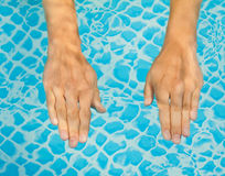 Young sweet woman's hand in a swimming pool Stock Image