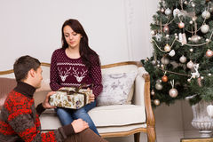Young Sweethearts Holding Gift Near Christmas Tree Royalty Free Stock Images