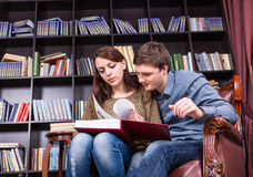 Young Sweethearts Reading a Literature at Library Royalty Free Stock Photography