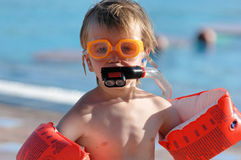 Young swimmer with floats. A boy stands by the poolside with floats on his arms and a snorkel and goggles on his face Stock Photo