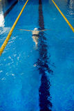 Young Swimmer in Pool. High angle shot of unrecognizable school age boy swimming fast face down underwater with large strokes in pool lane separated by yellow Stock Photo