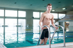 Young swimmer standing on the ladder Royalty Free Stock Photos