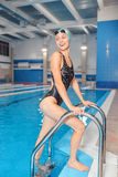 Young swimmer woman getting out of a swimming pool. Royalty Free Stock Photography