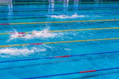 Young swimmers in outdoor swimming pool during competition. Health and fitness lifestyle concept with kids. Young swimmers in outdoor swimming pool during stock photo