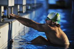 Young swimmmer on swimming start. Start position race concept with fit swimmer on swimming pool Stock Photos