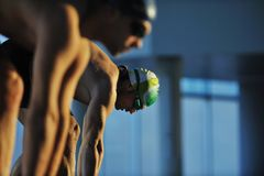 Young swimmmer on swimming start. Start position race concept with fit swimmer on swimming pool Royalty Free Stock Photo
