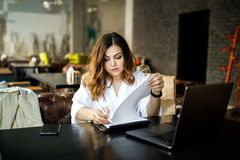 A young, sympathetic woman, not a thin-headed body building, sits in a cozy cafe, works at a computer, reviews documents. Business royalty free stock photo