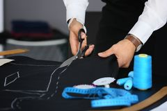 Young tailor cutting out suit detail. In atelier Royalty Free Stock Photography